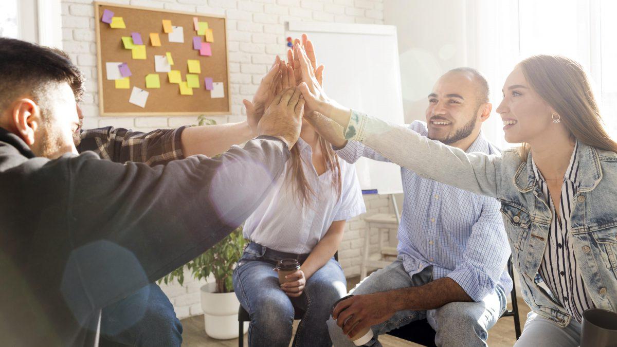 trabalhadores sentados com as mãos juntas dentro de uma sala